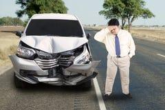Z nadwagą biznesmen z łamanym samochodem w drodze obraz royalty free