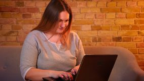 Z nadwagą długowłosy żeński freelancer siedzi na kanapie pracuje attentively z laptopem w wygodnej domowej atmosferze zdjęcie wideo