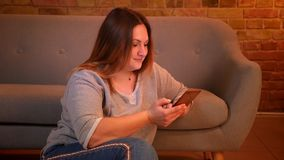 Z nadwagą długowłosy żeński freelancer siedzi na podłogowym działaniu z smartphone w wygodnej domowej atmosferze zdjęcie wideo