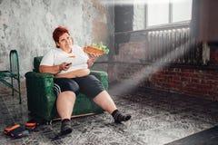 Z nadwagą kobieta ogląda TV, bulimic, grubas fotografia royalty free