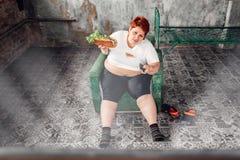 Z nadwagą kobieta ogląda TV, bulimic, grubas zdjęcie stock
