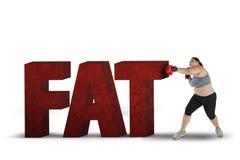 Z nadwagą kobieta uderza pięścią słowo sadło Fotografia Stock