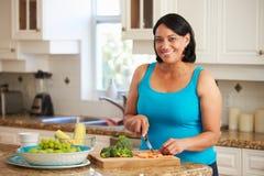 Z nadwagą kobiety narządzania warzywa w kuchni zdjęcia stock