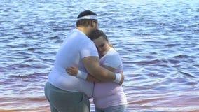 Z nadwagą mężczyzna ściska jego ślicznej tłuściuchnej dziewczyny blisko rzeki, czułości i miłości, zdjęcie wideo
