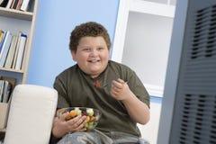 Z nadwagą chłopiec łasowania puchar owoc Przed TV Zdjęcia Stock