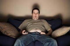 Z nadwagą slob ogląda TV Obrazy Stock
