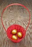 Złoci Wielkanocni jajka w czerwonym koszu. fotografia stock