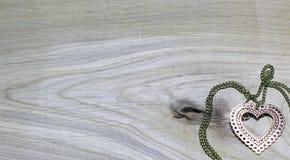 Złocisty serce na lekkim drewnianym tle Zdjęcia Royalty Free