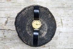 Z?ocisty wristwatch z rzemienn? patk? na drewnianym tle zdjęcia royalty free