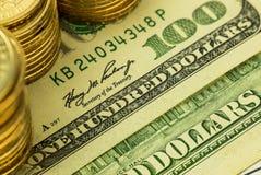 Złote monety na sto dolarach banknotów Obrazy Stock