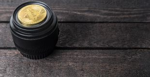 Złoty bitcoin kłaść na kamera obiektywie na drewnianym tle zdjęcie royalty free