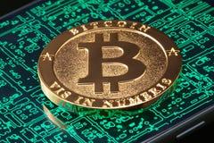 Złoty bitcoin na smartphone Fotografia Stock