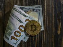 Z?oty Bitcoin na USA dolarach Cyfrowej waluta w g?r? drewnianego t?a dalej Istne monety bitcoin na banknotach sto zdjęcia stock