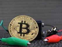 Złoty Bitcoin z baterii i aligatora klamerkami Fotografia Stock