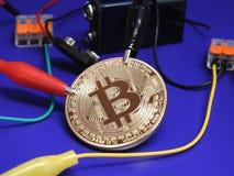 Złoty Bitcoin z baterii i aligatora klamerkami Zdjęcie Royalty Free