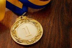 Złoty medal na drewnianym stole Zdjęcia Royalty Free