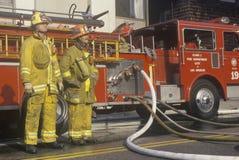 Z pożarniczym wąż elastyczny strażaka działanie Zdjęcia Royalty Free