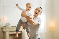 Z podnieceniem śmieszny ojciec stawia jego dziecka w powietrzu i ono uśmiecha się radośnie fotografia stock