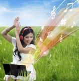 Z podnieceniem żeńska ściąganie muzyka od laptopu - plenerowego obrazy stock