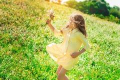 Z podnieceniem żeński dzieciak bawić się na łące z kwiatami zdjęcia royalty free