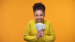Z podnieceniem afroamerykańska kobieta trzyma wiązkę dolary, loteryjny zwycięzca, pomyślność zdjęcie wideo