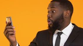 Z podnieceniem amerykanina mężczyzna wskazuje palec smartphone, online bankowość usługa zbiory