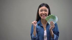Z podnieceniem Azjatycka kobieta pokazuje euro banknoty na kamerze, loteryjny zwycięzca, pomyślność zbiory