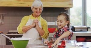 Z podnieceniem babcia opowiada dziewczyna podczas gdy przygotowywający ciastka 4K 4k zbiory
