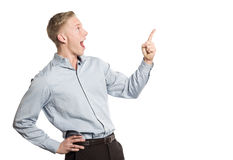 Zdziwiony biznesmen wskazuje palec przy pustą przestrzenią dla teksta. Zdjęcia Stock