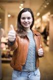 Z podnieceniem brunetka pozuje w sklepie odzieżowym i ono uśmiecha się Zdjęcia Stock