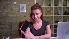 Z podnieceniem caucasian biznesowa kobieta jest przyglądająca jej telefonu ekran szczęśliwie i brać selfies podczas gdy siedzący