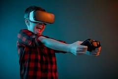 Z podnieceniem chłopiec bawić się gamepad w VR szkłach Fotografia Stock