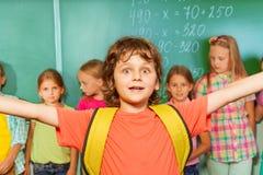 Z podnieceniem chłopiec z rękami w oddaleniu jest ubranym blisko chalkboard Zdjęcia Stock