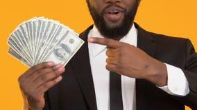 Z podnieceniem czarny męski wskazuje palec wiązka dolary, kredytowe usługi, deponuje pieniądze zdjęcie wideo