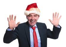 Z podnieceniem dojrzały biznesowy mężczyzna jest ubranym Santa Claus kapelusz Zdjęcia Royalty Free