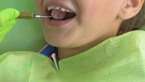 Z podnieceniem dzieciaka obsiadanie w stomatologicznym krześle, doktorscy egzamininuje zęby z dodatku specjalnego lustrem zbiory wideo
