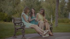 Z podnieceniem dziewczyny ogląda środek zawartość na telefonie komórkowym zbiory