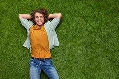 Z podnieceniem facet relaksuje na trawie obrazy stock