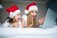 Z podnieceniem i niespodzianka córka na poranku bożonarodzeniowy i matka używać laptop w łóżku fotografia stock