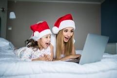 Z podnieceniem i niespodzianka córka na poranku bożonarodzeniowy i matka używać laptop w łóżku zdjęcia royalty free