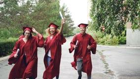 Z podnieceniem kończy studia ucznie jest ubranym togi biegają z dyplomami na kampusu terytorium i tradycyjni kapelusze, ono jest zdjęcie wideo