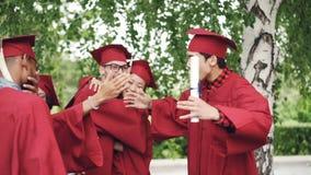 Z podnieceniem kobieta absolwenci i młodzi człowiecy robią wysokości, obejmowaniu i roześmianemu mienie dyplomów świętować, zdjęcie wideo