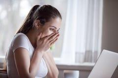 Z podnieceniem kobieta czyta niespodziewan? dobr? wiadomo?? na komputerze w domu fotografia royalty free