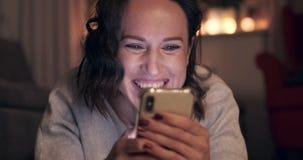 Z podnieceniem kobieta używa telefon komórkowego przy nocą zbiory