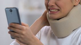 Z podnieceniem kobieta w karkowym kołnierza mienia smartphone, czuciowy ostry szyja ból zbiory wideo