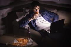 Z podnieceniem mężczyzna łasowania pizza i dopatrywanie film na laptopie obrazy stock