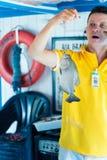 Z podnieceniem mężczyzna w żółtej tshirt mienia ryba na linii Fotografia Royalty Free