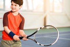 Z podnieceniem męski dziecko ma zabawę na tenisowym sądzie Fotografia Stock