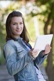 Z podnieceniem młoda kobieta czyta cyfrową pastylkę plenerową obrazy royalty free
