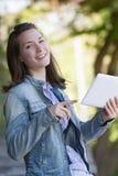 Z podnieceniem młoda kobieta czyta cyfrową pastylkę plenerową fotografia stock